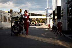 Un mécanicien Ferrari avec des pneus Pirelli dans le paddock