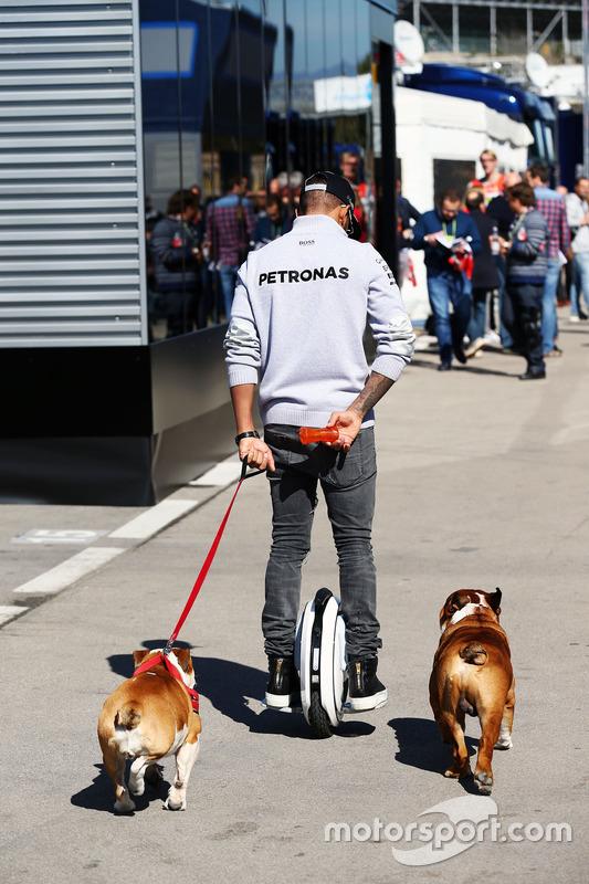 Lewis Hamilton, de Mercedes AMG F1 en un hoverboard en el paddock con sus perros Roscoe y Coco