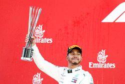 Lewis Hamilton, Mercedes AMG F1, raises his trophy in celebration on the podium