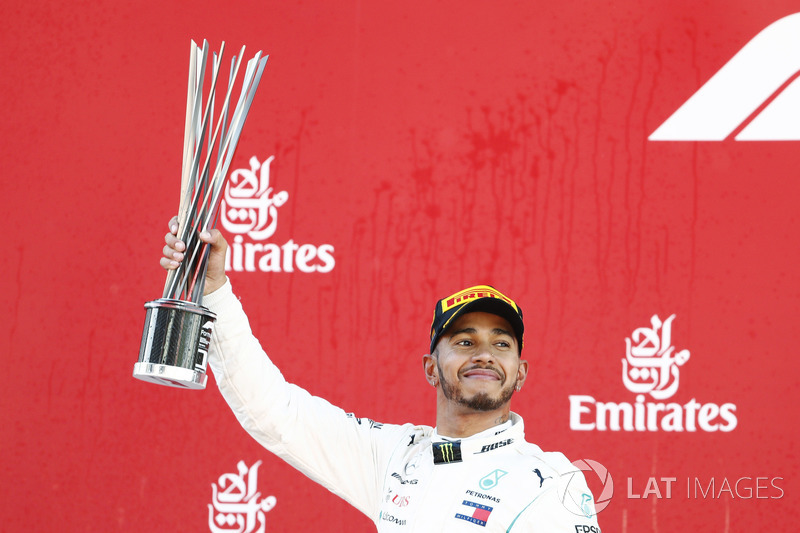 Lewis Hamilton, Mercedes AMG F1, raises his trophy in celebration on the podium