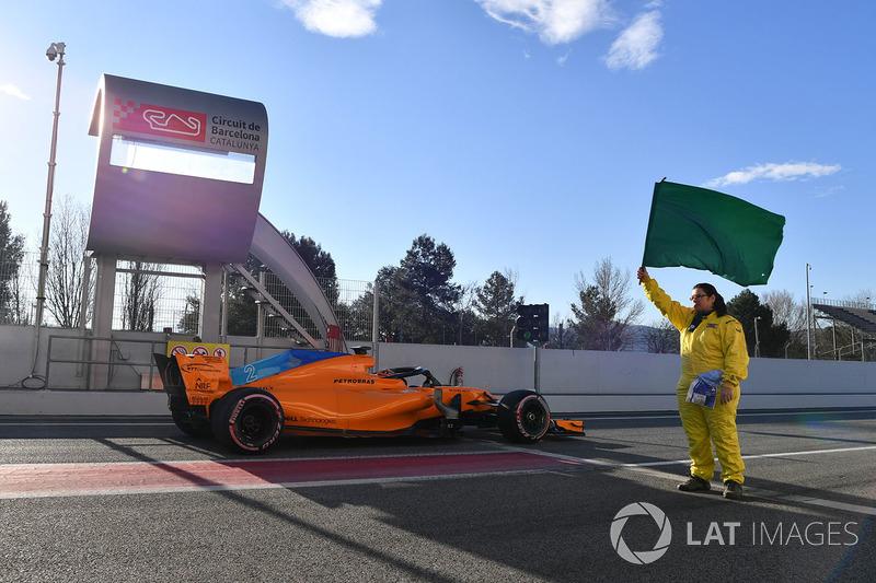 Stoffel Vandoorne, McLaren MCL33, y un comisario con la bandera verde
