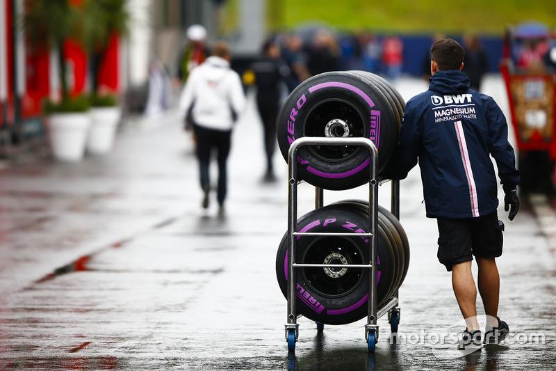 Un meccanico Force India attraversa il paddock con degli pneumatici Pirelli