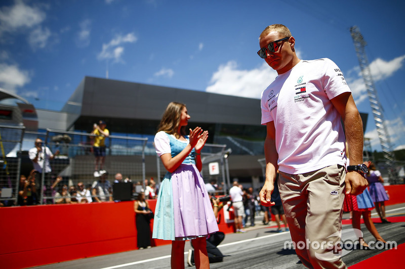 Grid Girls in national costume flank the drivers parade as Valtteri Bottas, Mercedes AMG F1, passes
