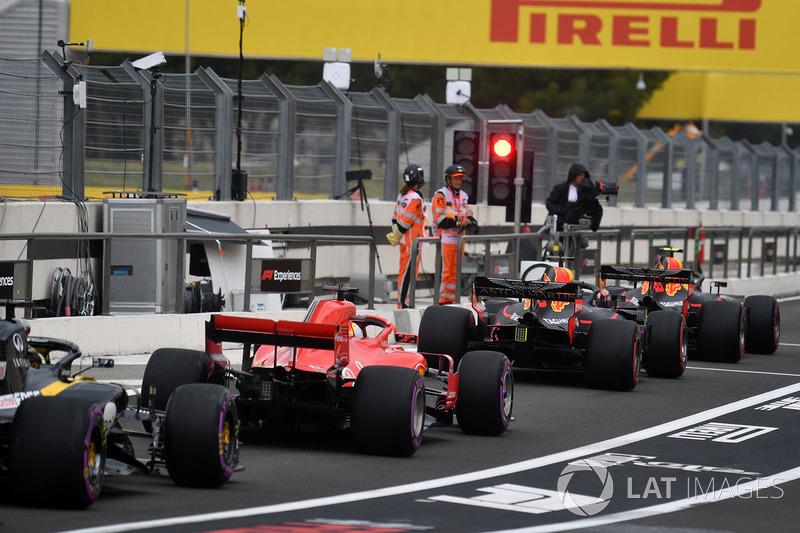 Los coches hacen cola en la luz roja en el carril de boxes