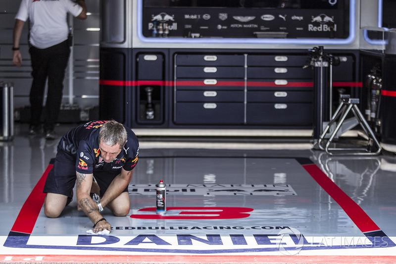 Un mécanicien de Red Bull Racing nettoie le sol du garage