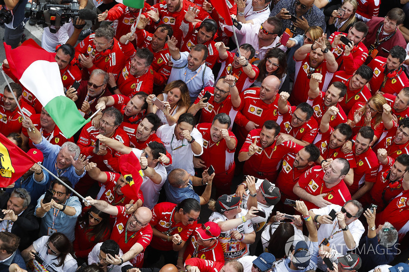 Ferrari team members gather beneath the podium to celebrate victory