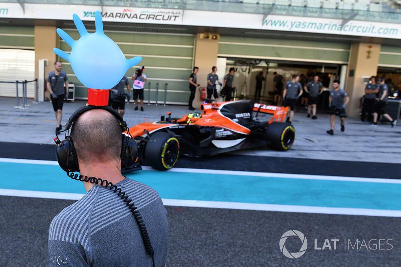 Lando Norris, McLaren MCL32 y un mecánico de McLaren con un guante sobre sus cascos