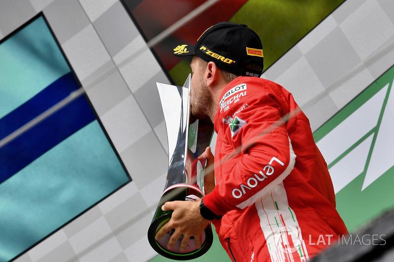 Race winner Sebastian Vettel, Ferrari celebrates and kisses the trophy on the podium