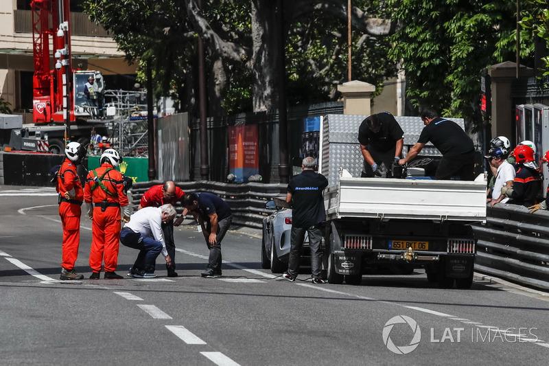 Charlie Whiting, delegado de la FIA supervisa las reparaciones de una cubierta de desagüe suelta que provocó que el FP2 se marcara con una bandera roja