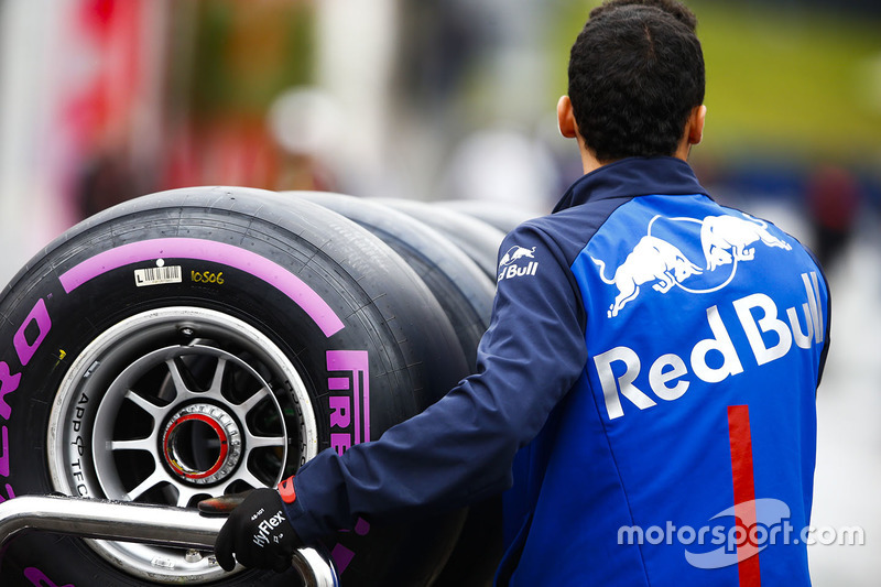 A Toro Rosso team member pushes a trolley of Pirelli tyres through the paddock