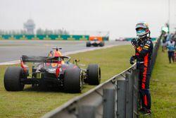Daniel Ricciardo, Red Bull Racing, waits next to his stricken car