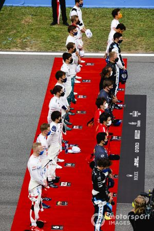 The drivers stand in line for the national anthem prior to the start