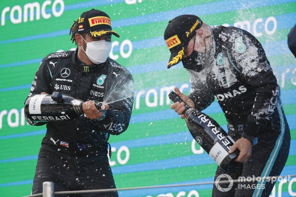 Lewis Hamilton, Mercedes, 1 ° posizione, e Valtteri Bottas, Mercedes, 3 ° posizione, spruzzano Champagne sul podio