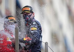Max Verstappen, Red Bull Racing, 1st position, and Carlos Sainz Jr., Ferrari, 2nd position, spray Champagne on the podium