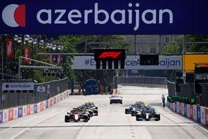 Charles Leclerc, Ferrari SF21, and Lewis Hamilton, Mercedes W12, lead the field away at the start
