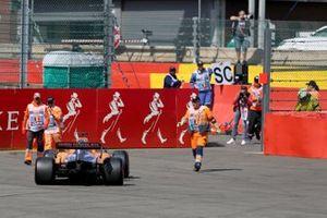 Los oficiales recuperan el coche de Carlos Sainz Jr, McLaren MCL34, después de retirarse con un problema técnico