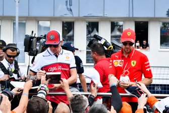 Kimi Raikkonen, Alfa Romeo Racing, and Sebastian Vettel, Ferrari, sign autographs for fans