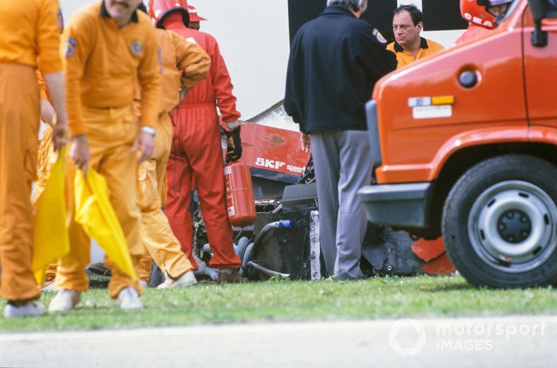 Marshals attend Gerhard Berger's Ferrari 640 after an accident