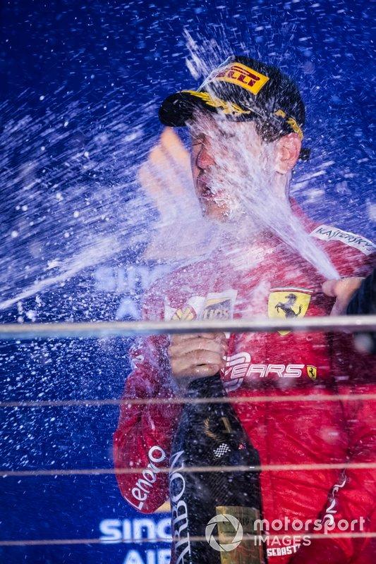 Sebastian Vettel, Ferrari, primo classificato, viene bagnato dallo Champagne sul podio