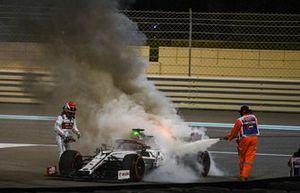 A marshal extinguishes the flames on the car of Kimi Raikkonen, Alfa Romeo Racing C39