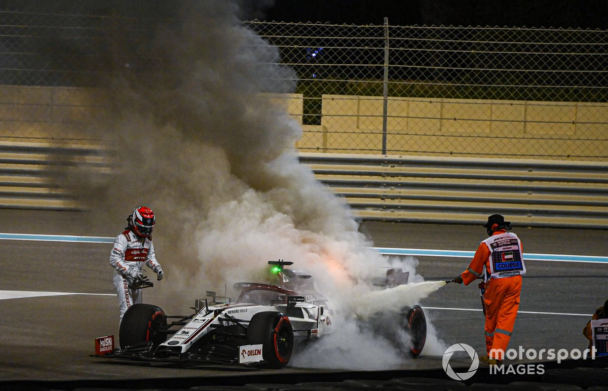 A marshal extinguishes the flames on the car of Kimi Raikkonen, Alfa Romeo Racing C39