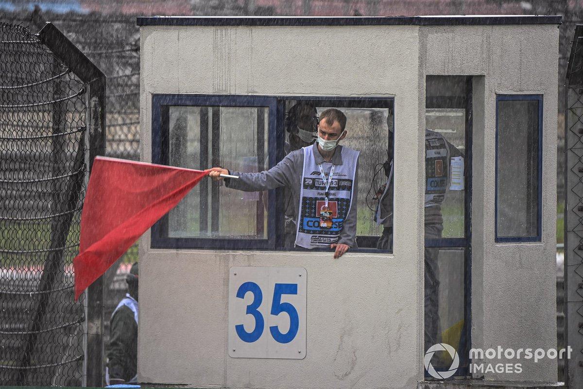 Un oficial de pista agita una bandera roja