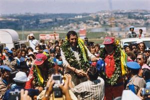 Carlos Pace celebrates his first and only victory in front of his home crowd with fellow Brazilian Emerson Fittipaldi, 2nd position, and Jochen Mass, 3rd position