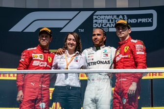 Sebastian Vettel, Ferrari, 2nd position, the Mercedes Constructors trophy delegate, Lewis Hamilton, Mercedes AMG F1, 1st position, and Charles Leclerc, Ferrari, 3rd position, on the podium