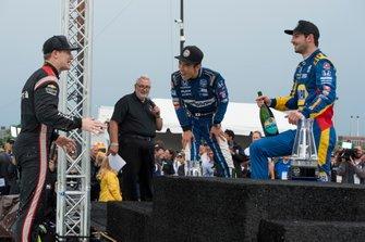 Takuma Sato, Rahal Letterman Lanigan Racing Honda, y Alexander Rossi, Andretti Autosport Honda, ríen con el ganador de la carrera Josef Newgarden, el equipo Penske Chevrolet luego de que Newgarden se subió a la Fuente Scott para celebrar su victoria.