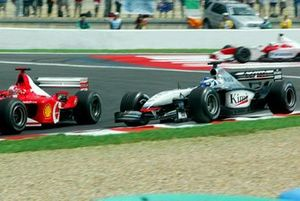 Kimi Raikkonen, McLaren Mercedes MP4/17 runs wide, Michael Schumacher, Ferrari F2002 pass