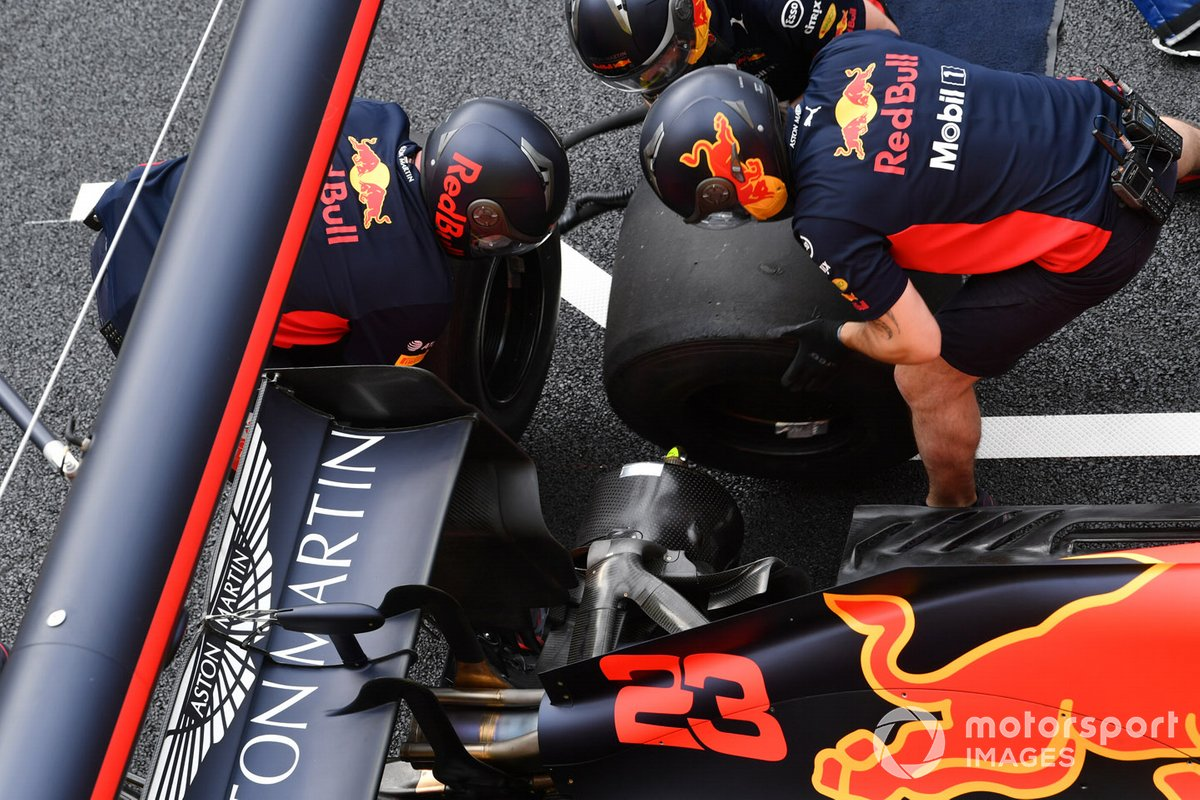 Red Bull Racing mechanics change a rear tyre during a practise pit stop