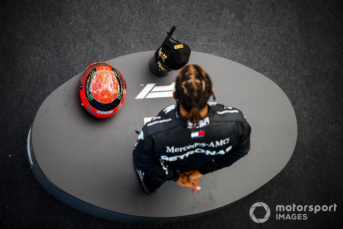 Lewis Hamilton, Mercedes-AMG F1, 1ª posición, en el podio con su trofeo y el casco de Michael Schumacher