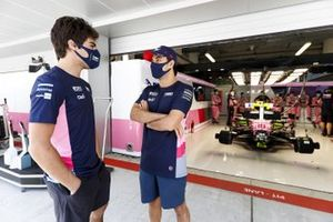 Lance Stroll, Racing Point, and Sergio Perez, Racing Point, talk outside the garage