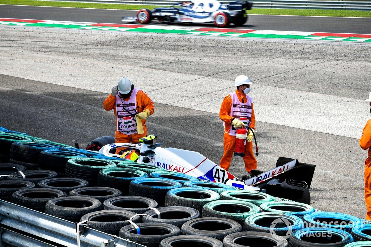 Los oficiales de pista asisten a Mick Schumacher, Haas VF-21, tras su accidente en la FP3