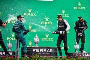 Le deuxième Sebastian Vettel, Aston Martin, le vainqueur Esteban Ocon, Alpine F1, et le troisième Lewis Hamilton, Mercedes, avec le Champagne sur le podium
