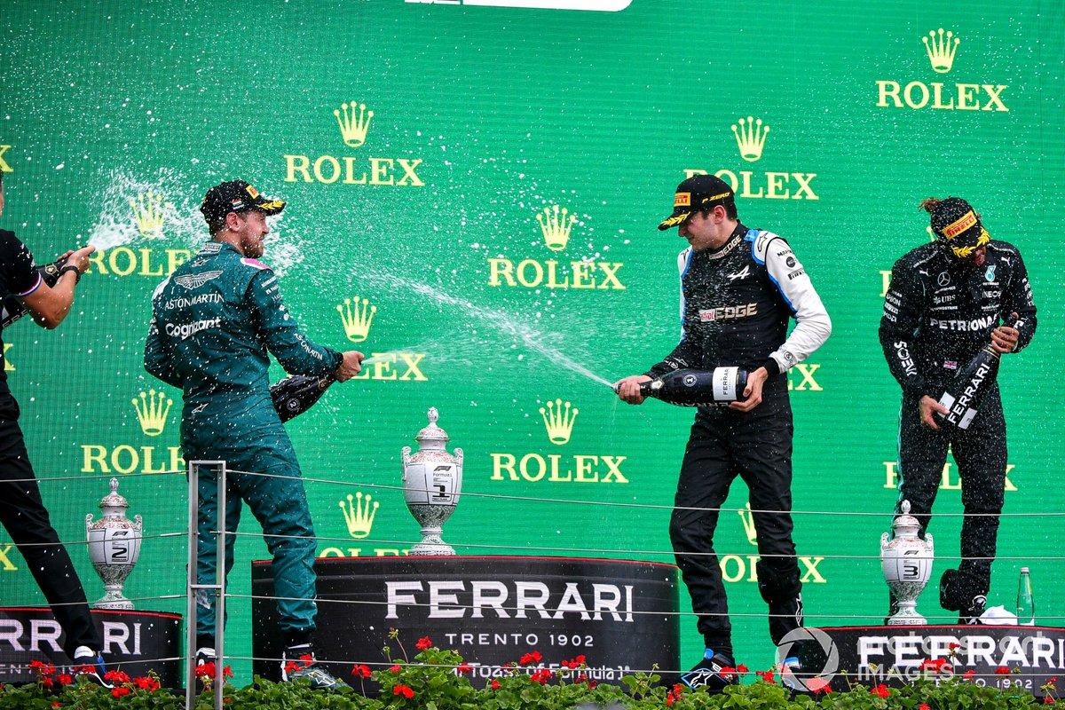Sebastian Vettel, Aston Martin, secondo classificato, Esteban Ocon, Alpine F1, primo classificato, e Lewis Hamilton, Mercedes, terzo classificato, spruzzano Champagne sul podio