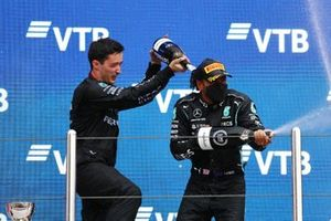 Lewis Hamilton, Mercedes, 1st position, and the Mercedes trophy delegate celebrate with Champagne on the podium