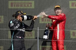 Lewis Hamilton, Mercedes, 1st position, and Charles Leclerc, Ferrari, 2nd position, spray Champagne on the podium