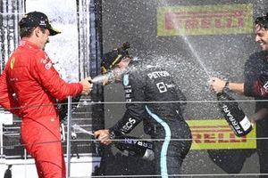 Charles Leclerc, Ferrari, 2nd position, Lewis Hamilton, Mercedes, 1st position, and the Mercedes trophy delegate celebrate with Champagne