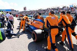 Daniel Ricciardo, McLaren MCL35M, arrives on the grid with mechanics