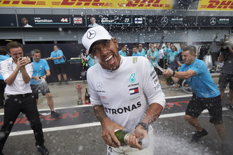 Lewis Hamilton, Mercedes AMG F1, sprays champagne in celebration of victory