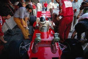 Йохен Риндт вылезает из Lotus 72C Ford. За ним наблюдают австрийский журналист Гельмут Цвикль, механик Херби Блаш и руководитель команды Колин Чепмен