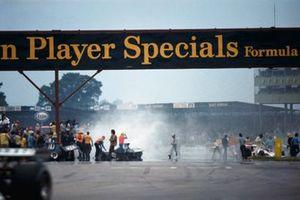 Lavoro di pulizia dopo un giro e l'incidente di massa dopo la partenza. Graham Hill esce dalla sua Ford Ombra DN1 sulla destra