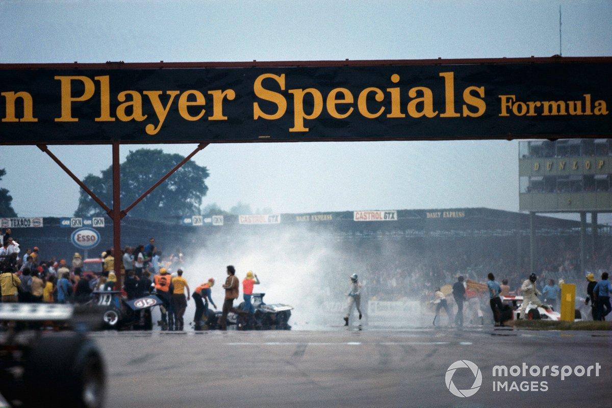 Trabajos de limpieza después del accidente en la primera vuelta. Graham Hill sale de su Shadow DN1 Ford a la derecha