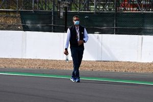 A member of the FIA walks the track
