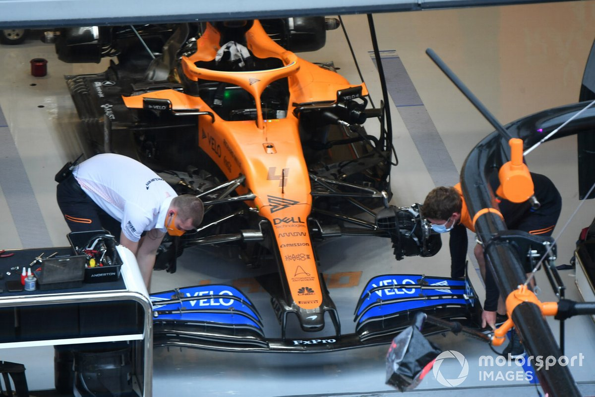 The Lando Norris McLaren MCL35 is worked on by mechanics in the team's garage