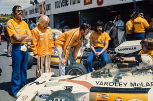 Denny Hulme sat in his McLaren M19C Ford in the pits with Alastair Caldwell, Patty McLaren and engineers