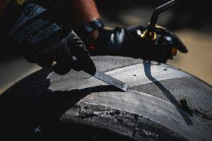 L'équipe de Helio Castroneves, Team Penske Chevrolet nettoient un pneu