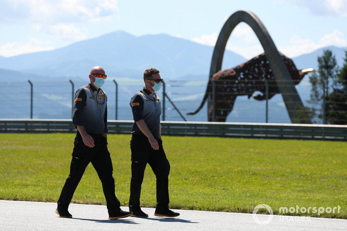 Pirelli personnel walk the track