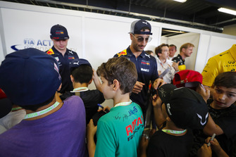 Max Verstappen, Red Bull Racing, and Daniel Ricciardo, Red Bull Racing, sign autographs for young fans